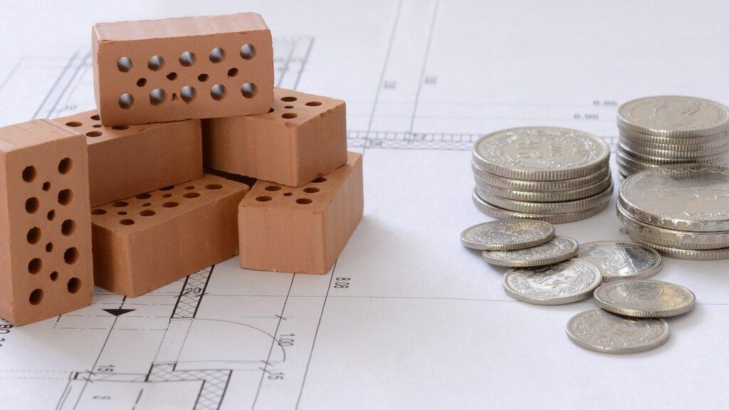 Baufinanzierung (Bauplan, Bauklötze und Euro-Münzen)