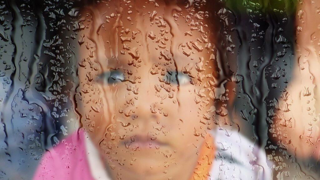 Trauriges Kind hinter verregneter Fensterscheibe