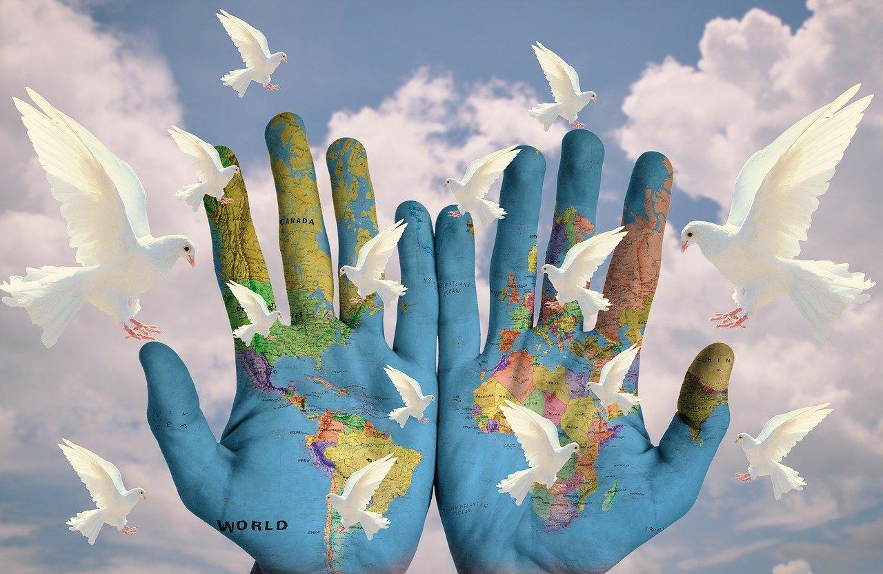 Weltfrieden (zahlreiche weiße Tauben vor dem Hintergrund aus zwei mit den Umrissen der Kontinente bemalten Händen und Wolken)